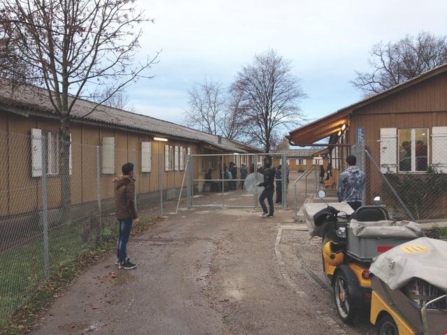 Das Bild zeigt die Schule, die in einer Art Baracken sind. Sie sind eingezäunt mit einem hohen Draht und einem grossen Tor. Die Bäume haben keine Blätter mehr. Es stehen einige junge Menschen vor der Türe.