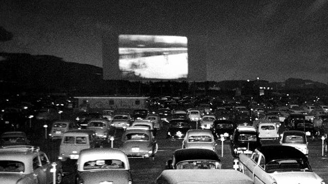 Ein altes schwarz-weiss-Foto: Auf einer Leinwand läuft ein Film, davor sind viele Autos prakiert.