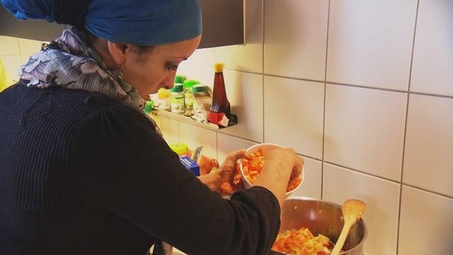 Eine Frau mit Kopftuch kocht ein muslimisches Feiertagsgericht.