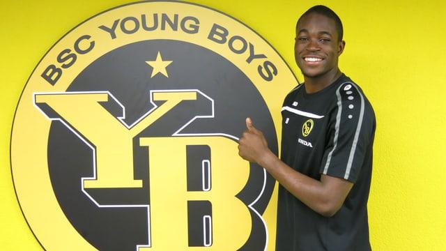 Yvon Mvogo neben einem YB-Logo an der Wand.