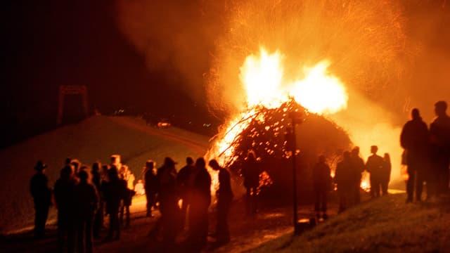 Leute stehen um einen Scheiterhaufen, der brennt.
