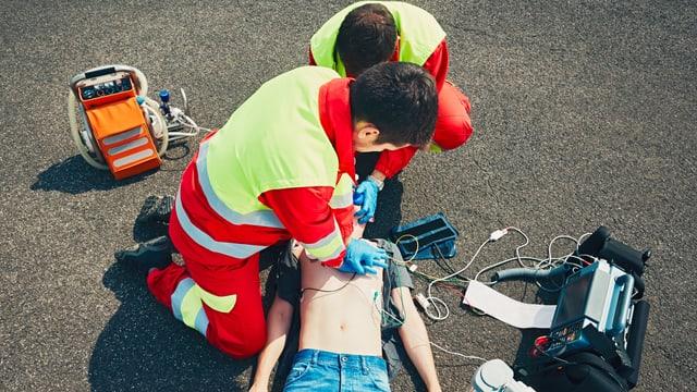 Männer in Rettungsuniformen reanimieren einen Patienten am Boden mit Herzmassage
