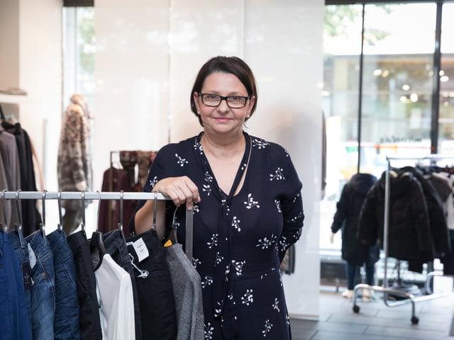 Eine Frau steht vor einer Garderobenstange in einem Kleiderladen.
