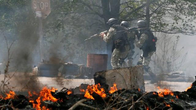 Bewaffnete Soldaten stehen vor brennenden Trümmern.