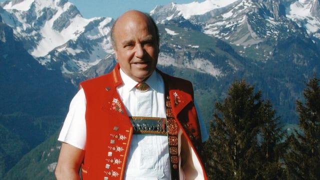 Dölf Mettler in Appenzeller Tracht vor einer Bergkulisse.