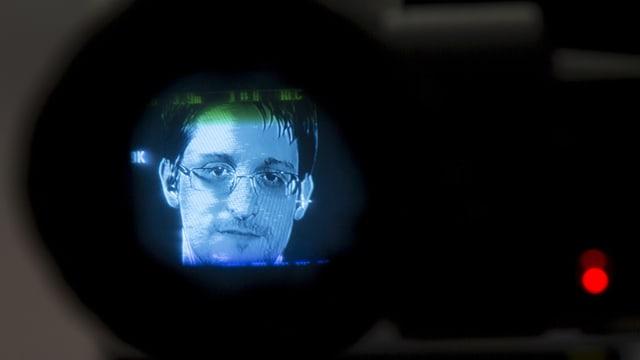 Snowden fotografiert als Bild durch eine Kameralinse.