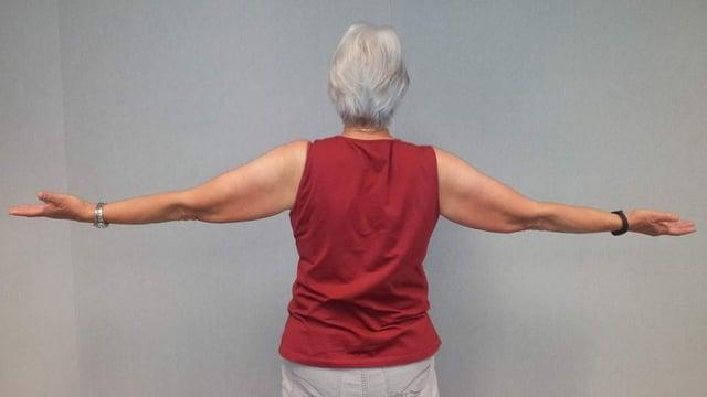 ältere Frau mit seitlich ausgestreckten Händen