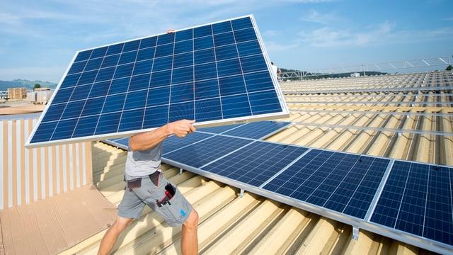Ein Mann trägt ein Solarpanel.