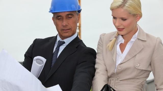 Ein Architekt mit Bauhelm zeigt einer jungen Frau Baupläne.