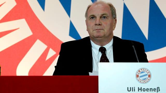 Der Präsident des FC Bayern München, Uli Hoeness vor einem Bayern-Wappen.