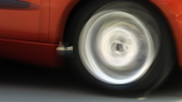 Rad von rotem Auto in Bewegung.