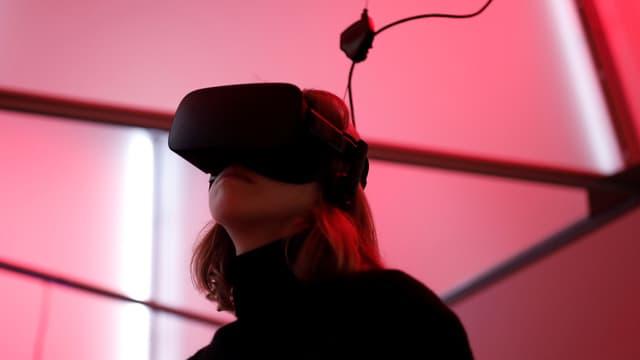 Eine Frau mit VR-Bitlle und Kabl in einem pink ausgeleuchteten Raum.