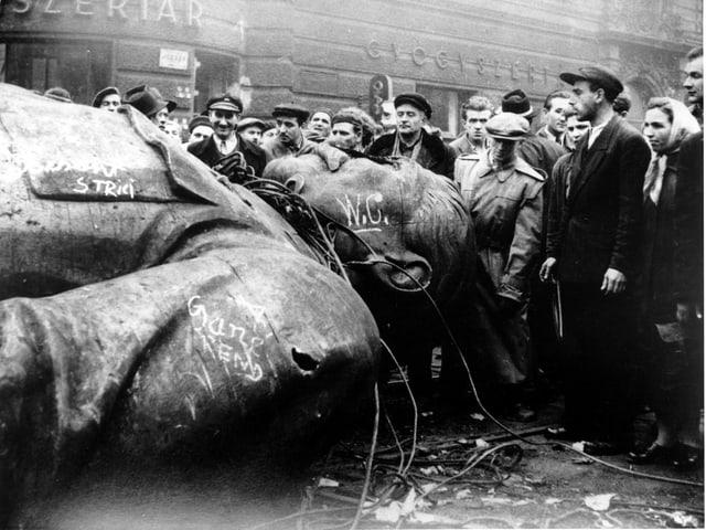 Menschen vor einer zu Fall gebrachten Stalin-Statue.