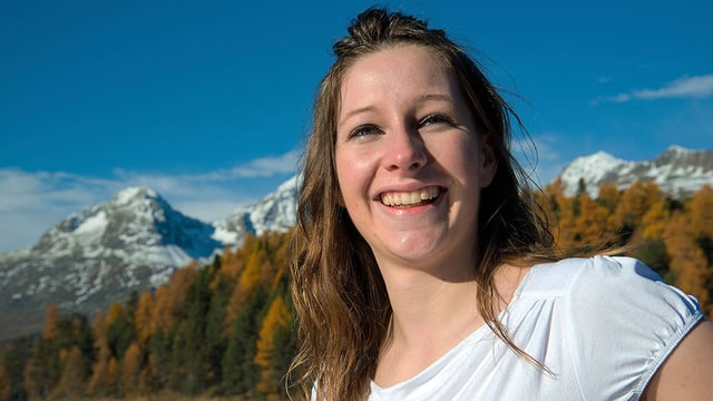 Eine junge Frau lächelt in die Kamera, inmitten der Engadiner Herbstlandschaft.