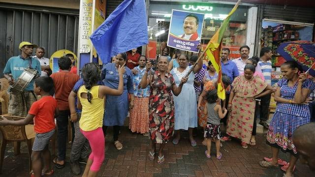 Frauen und einige Männer jubeln. Sie halten ein Plakat ihres neuen Präsidenten in die Luft.
