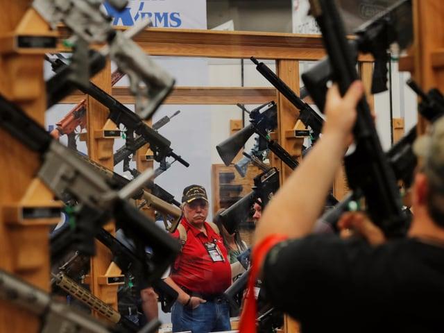 Mann steht vor Gewehren in einem Regal