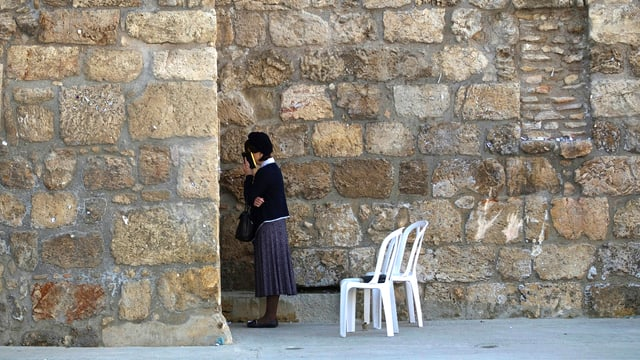 Eine Frau steht an der Klagemauer. Hinter ihr stehen zwei weisse Plastikstühle.