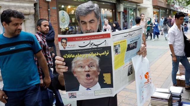 Mann liest Zeitung, auf Frontseite Bild von Trump