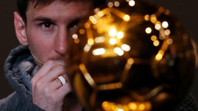 Lionel Messis Gesicht ist halb hinter einer goldenen Ball-Trophäe versteckt.
