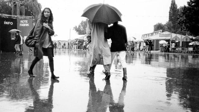Leute laufen im Regen.