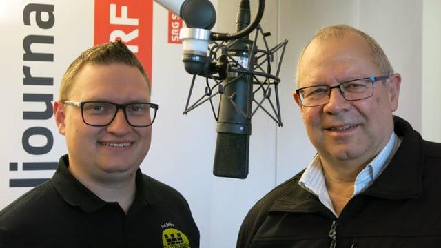 Zwei Männer stehen im Radiostudio und schauen in die Kamera. Man sieht zwischen Ihnen das Mikrophon.