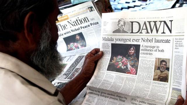 Ein Mann sieht sich die Titelseite einer Zeitung an, auf der ein Bild von Malala Yousafzai und ihrer Ehrung zu sehen ist.