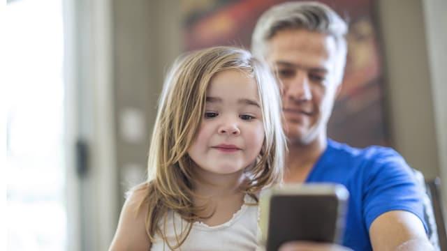Ein Vater mit Tochter und Smartphone in der Hand.