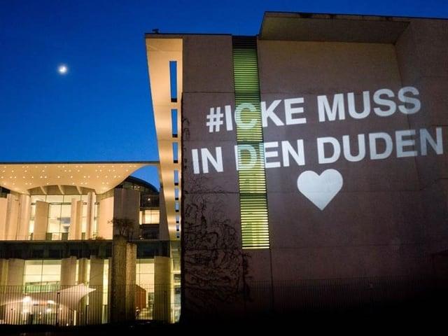 Kanzleramt bei Nacht, angestrahlt mit dem Satz «#ICKE MUSS IN DEN DUDEN» und ein Herz.
