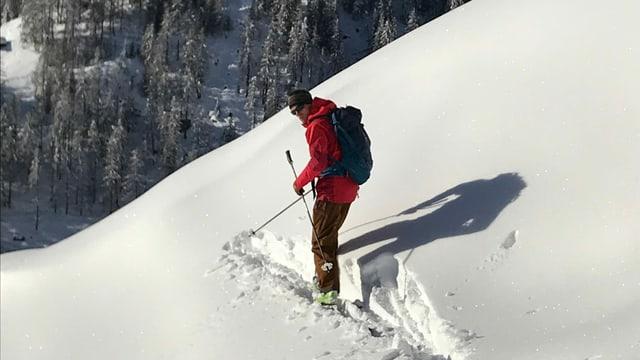 Der Lawinenbeobachter erklimmt den Berg mit Tourenski.