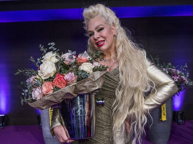 blonde Frau auf Bühne mit Blumen