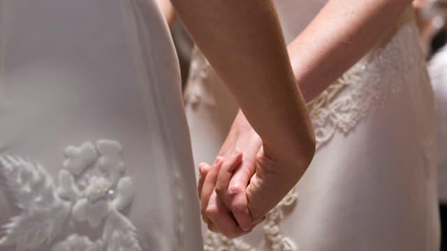 Zwei Frauen im Brautkleid halten sich an den Händen.