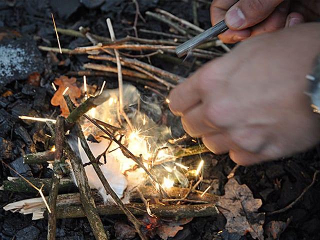 Feuer Anzünden, wie es Prepper planen: mit einem Tampon als Zunder.
