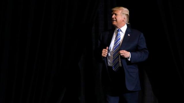 Trump aus der Ferne vor schwarzem Hintergrund.