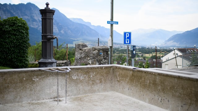 Trockener, leerer Brunnen. Im Hintergrund Blick auf das weite Churer Rheintal.