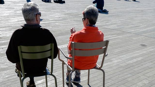 Senioren sitzen auf Stühlen auf dem Zürcher Sechseläutenplatz.