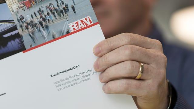 Ein Mann hält eine Broschüre des RAV.