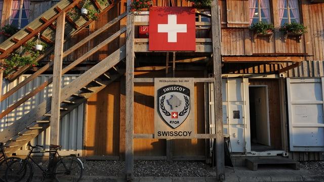Mit Holz verschalte Metallcontainer mit einer Schweizer Fahne und Geranien.