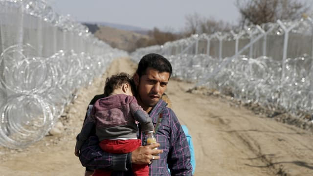 Ein Flüchtling an der griechisch-mazedonischen Grenze mit einem Kind auf dem Arm.
