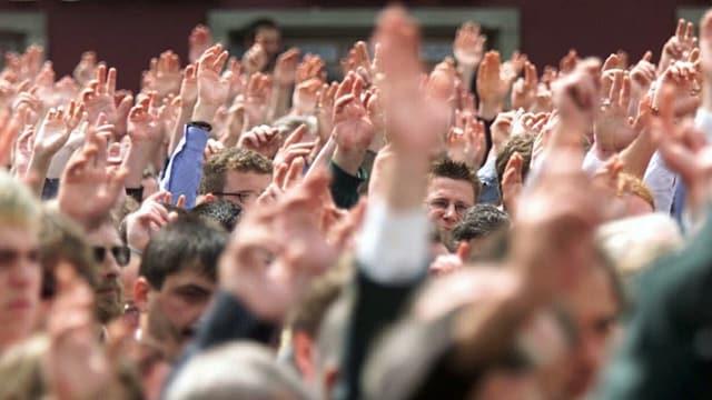 Eine Gruppe Leute mit erhobenen Händen