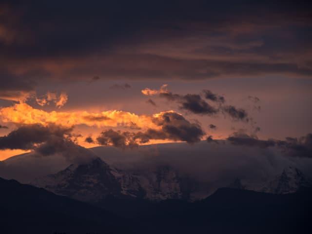 Bergmassiv, von hinten drücken Wolken darüber. Dämmerung mit goldenem Licht am Horizont, aber vielen Wolken.
