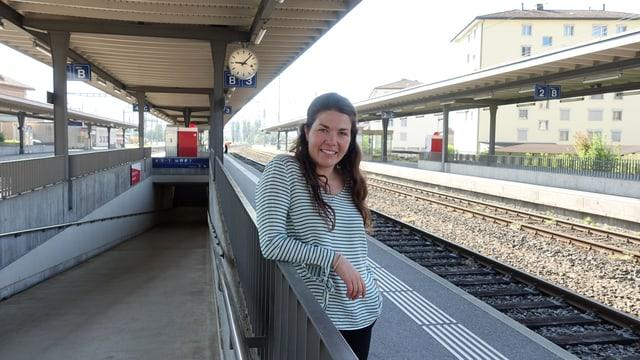 Junge Frau steht auf dem Perron am Bahnhof und lächelt freundlich in die Kamera