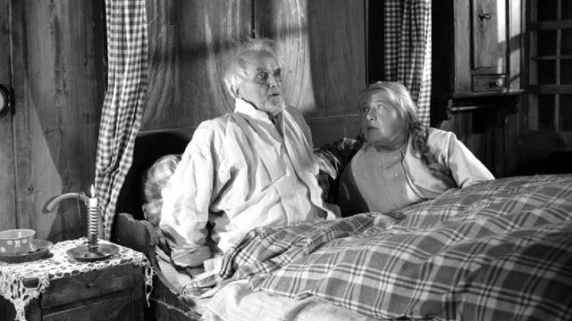 Ein älteres Ehepaar im Bett. Er sitzt aufgeschreckt im Bett, sie blickt besorgt zu ihm hoch.