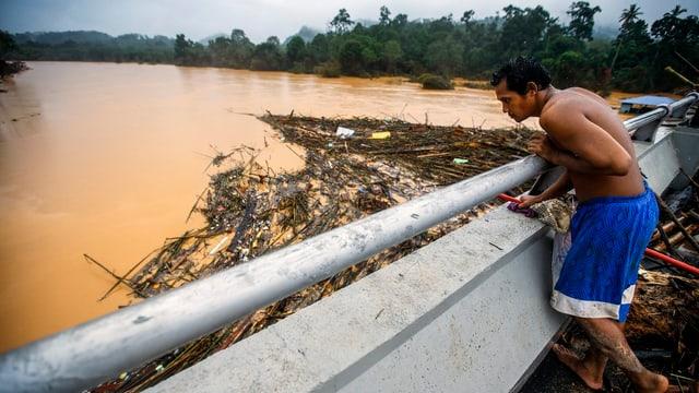 Ein Mann schaut auf einen überschwemmten Fluss.