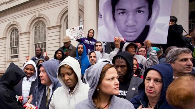 Eine Gruppe von Leuten protestiert mit Plakaten, die mit dem Gesicht von Martin beklebt sind, vor dem Gerichtsgebäude.