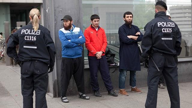 Drei Männer stehen einer Polizistin und einem Polizisten gegenüber