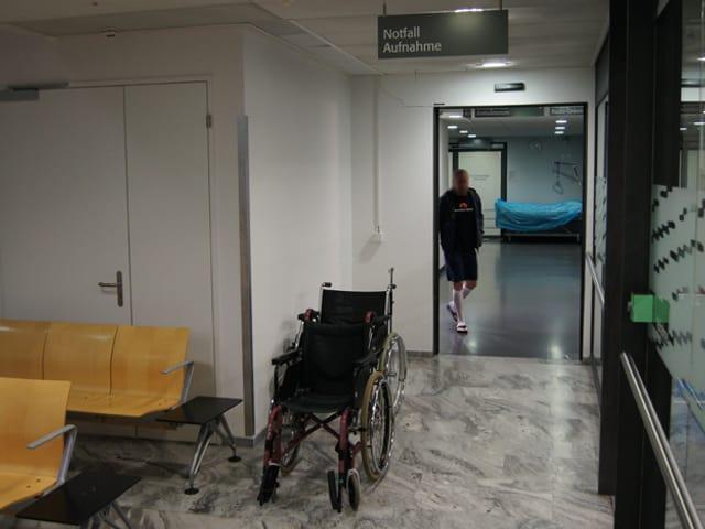 Ein Gang, auf der linken Seite Stühle und Rollstühle, dahinter eine Türe aus der ein Mann rausläuft.