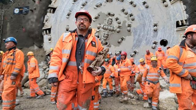 Bauarbeiter in orangen Kleidern vor einer Tunnelbohrmaschine.