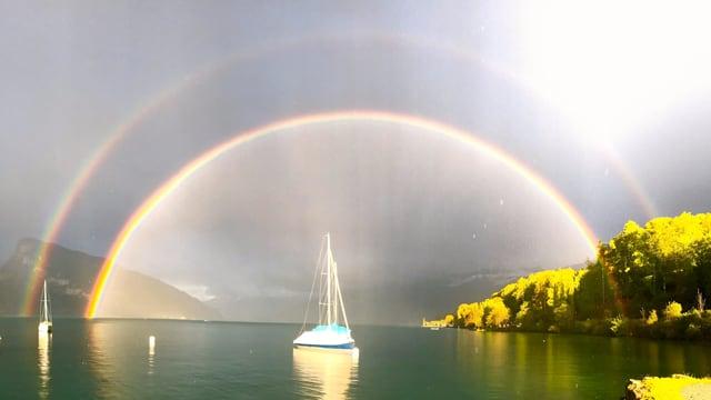 Regenbogen, in der Mitte ein Schiff.