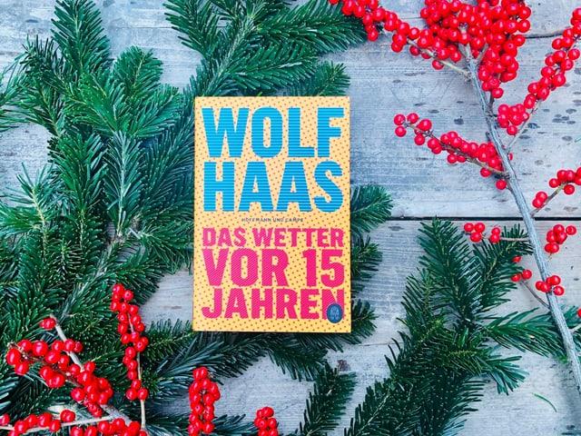 «Das Wetter vor 15 Jahren» von Wolf Haas liegt auf einem Tisch mit Weihnachtsdekoration