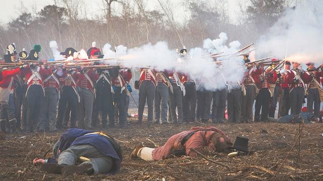 Männer in historischen Uniformen umgeben von Pulverdampf.